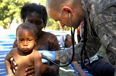 Capt. Mark Poirier gives medical attention to a baby in Haiti