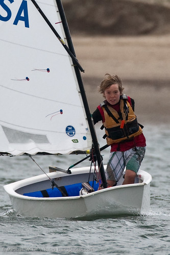 Energetic skilled young boy, this youngster from Morro Bay Yacht Club Junior Lifeguard Sailboat Race in Morro Bay, CA., demonstrates sailing skills as he negotiates a turn coming about.