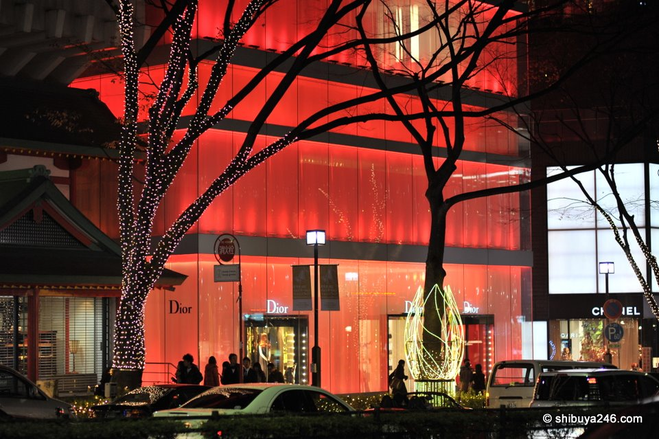 The Dior red building glowing in the night shadows.
