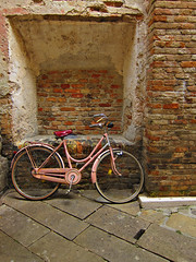 pink bike and brick wall
