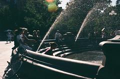 Read in Rain. (Pedro Silvares) Tags: park nyc usa newyork film water fountain manhattan washingtonsquarepark september washingtonsquare nikkor nikonfg 50mmf12ais