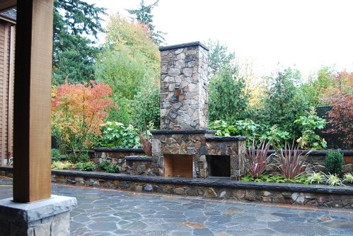 stone patio pillars plantings seatwall outdoorfireplace outdoorliving woodhutch alloregonlandscaping