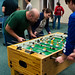 Micah Hurst, residence director, plays foosball in the game room during late night in the commons.