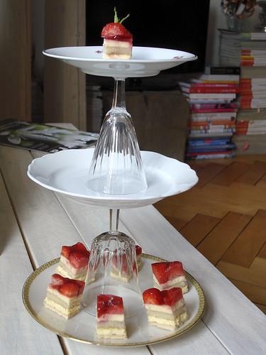 Etagere aus Teller und Gläser mit Erdbeertörtchen