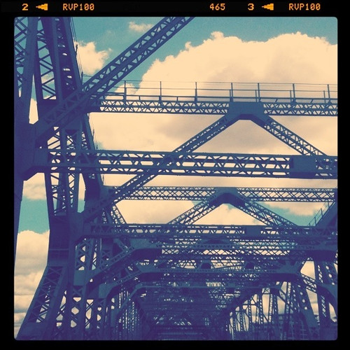 A photo of the metal structure that the Story Bridge is made out of. The section of bridge in the photo is only an abstract, and you can see the blue sky spotted with clouds through the scaffolding.