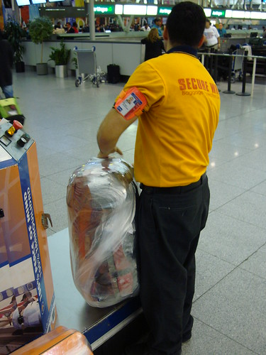 Wrapping luggage in plastic at JFK airport, USA