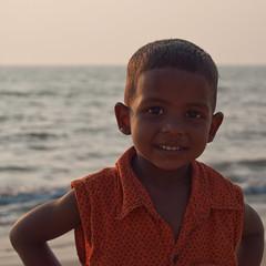 Curious Boy (serpil.senger) Tags: boy sea orange india water smile eyes kerala cheraibeach vypeenisland d5000