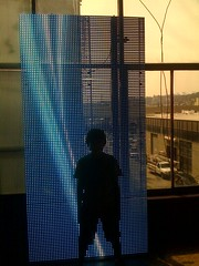 Alex stands at LED wall at Brewery Artwalk