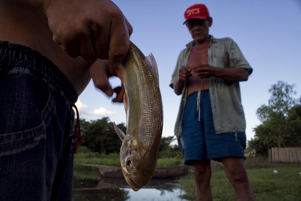 Un niño sostiene un pescado mientras comparte consejos con un viejo pescador. (Puerto La Niña, San Pedro, Paraguay - Tetsu Espósito)