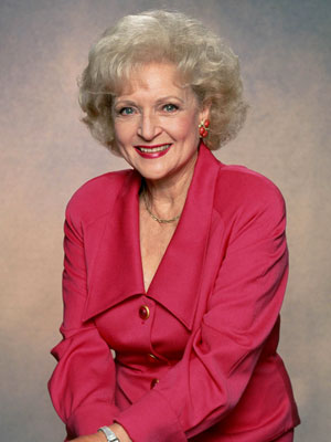 a photo portrait of Betty White. She is smiling and wearing a pink suit. Her hands are folded in her lap.