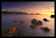 The Twilight (anthonyko) Tags: ocean longexposure blue red sea newzealand orange snow mountains sunrise rocks pacificocean southisland seawardkaikourarange