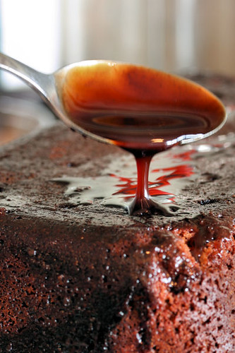 spooning chocolate syrup over cake 8775 R