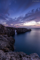 Menorca Sunset III. [Explored & FP 06-29-2017] (dasanes77) Tags: canoneos6d canonef1635mmf4lisusm tripod landscape seascape cloudscape waterscape clouds cloudsmovement windy horizon sea reflections shadows bluehour longexposure rocks cliff nature naturallight sunset sun blue orange menorca pontdengil