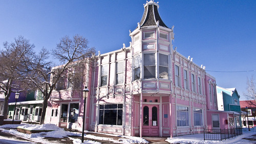 A pink storybook victorian building against a blue sky. It's closed.