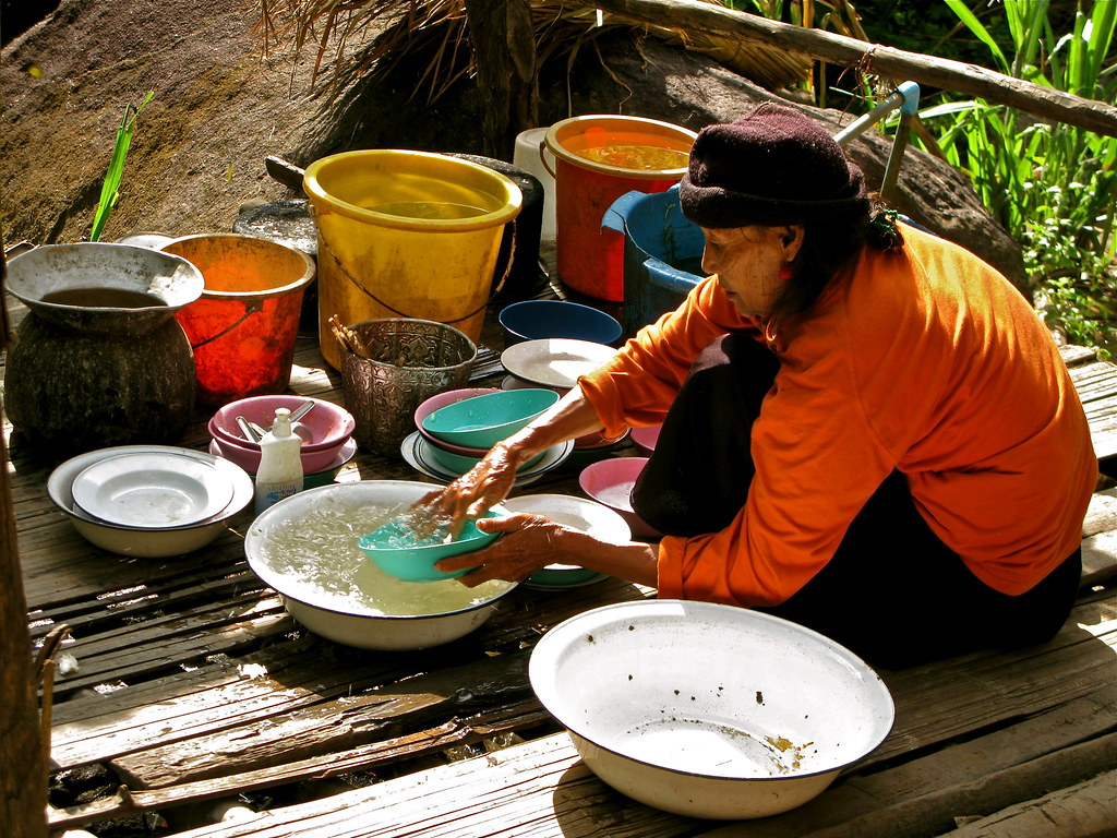 Chiang Mai, Trekking. An old lady washing dishes in a jungle village