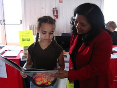 JJML's Aracely Garcia sharing a book from the Library's collection with a young fair goer.