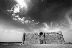 Qasr Al Kharana ( ) (... Arjun) Tags: sky blackandwhite bw 15fav cloud distortion castle monochrome clouds 1025fav 510fav iso100 blackwhite lawrence ancient ruins asia view citadel islam wide perspective middleeast dramatic surreal kingdom wideangle monotone 100v10f jordan textures f90 remote lawrenceofarabia hedonism islamic 2010 qasr rectilinear ruleofthirds easterndesert leadinglines 17mm  hashemite  canonef1740mmf4l offthebeatentrack desertcastle bluelist  qasralkharana  kharaneh canoneos5dmarkii canon5dmarkii  desertcitadel gettyvacation2010