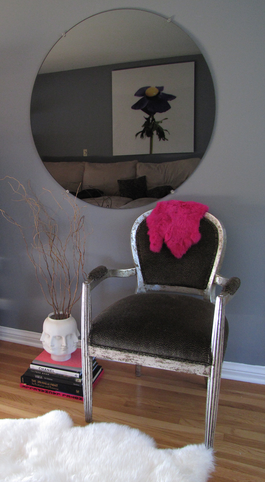 round mirror+nook+chair+face vase+sheep skin rug -cropped