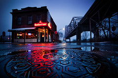 Manhole Bridge Tavern II (Notley) Tags: city winter usa snow reflection ice water colors weather architecture bar night lights evening stlouis landing reflect tavern bluehour manhole february nocturne manholecover 2010 stlouismissouri lacledeslanding thebluehour 10thavenue sundeckers notley snowyweather abigfave notleyhawkins missouriphotography httpwwwnotleyhawkinscom notleyhawkinsphotography