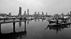 Souq Sharq Marina and the City ! (Saad Al-Enezi) Tags: city sea bw cloud beach water clouds marina boats nikon skies towers shy balckandwhite kuwait dhows souq souqsharq sharq d300 reflectins bludings saadalenezi