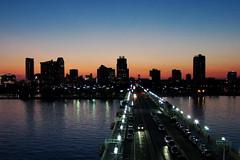 Goodnight Tampa Bay (AlyeceT) Tags: street longexposure sunset sky sun reflection water silhouette skyline night stpetersburg evening cityscape tampabay florida streetlights mywinners goldstaraward goldstarawardgoldmedalwinner sooccrop