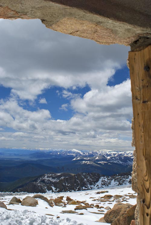 Looking out a rustic window from the ruins of a chalet at the very top of Mount Evans at an elevation of 14,264' shows a scenic mountain landscape as far as the eye can see.