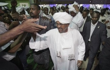 Sudan's president Omar al-Bashir, center, is congratulated by his supporters at the ruling party headquarters in Khartoum, Sudan, Monday, April 26, 2010. by Pan-African News Wire File Photos