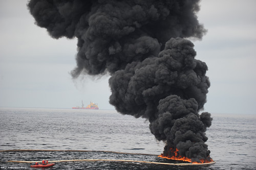"Gathered concentrated oil burns during a controlled oil fire in the Gulf of Mexico May 5, 2010. The U.S. Coast Guard working in partnership with BP PLC, local residents, and other federal agencies conducted the ""in situ burn"" to aid in preventing the spread of oil following the April 20 explosion on Mobile Offshore Drilling Unit Deepwater Horizon. (U.S. Navy photo by Mass Communication Specialist 2nd Justin E. Stumberg/Released)"