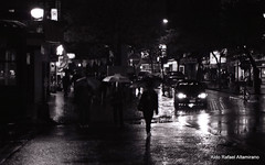 Rain (Rafakoy) Tags: city light people bw white black reflection cars film car rain night 35mm reflections dark 50mm lights photo kodak pavement f100 nikonf100 epson v600 perfection nikkoraf50mmf18d kodakplusx125 agfarodinal150 epsonv600 epsonperfectionv600 aldorafaelaltamirano rafaelaltamirano aldoraltamirano