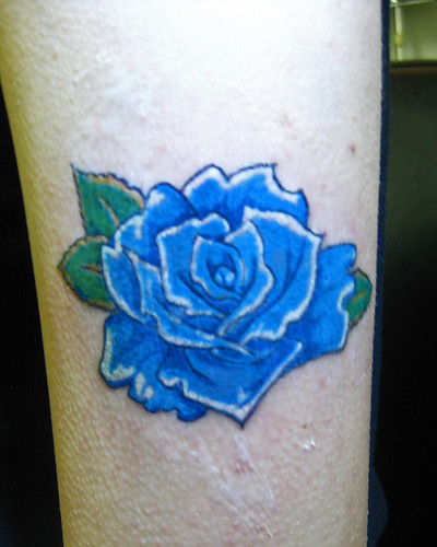 blue rose tattoo by Mikey Blackbird. a bright blue rose on the forearm