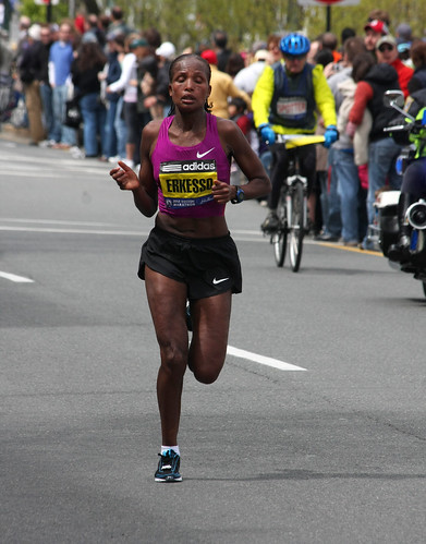 Competitor Teyba Erkesso in the Boston Marathon. She is a Black woman wearing athletic shorts and a tank top and is near the end of the course, sweating heavily.