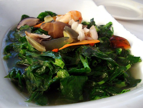 A dish of cooked dark green mangetout leaves garnished with pieces of century egg (皮蛋) and peeled prawns.  The leaves sit in a pool of pale-coloured stock.