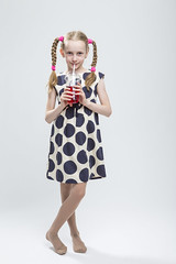 Portrait Of Smiling Caucasian LIttle Girl With Pigtails Standing Barefoot in Polka Dot Dress with Cup of Red Juice. Drinking Through Straw. (DmitryMorgan) Tags: 1 710years adorable baby beautiful blond caucasian cheerful child childhood cup daughter dress drink drinking european expression female fun girl holding human joy kid liquid little love model mood one pigtails polkadot portrait positive preschooler red school schoolgirl small smile smiling straw studio white young