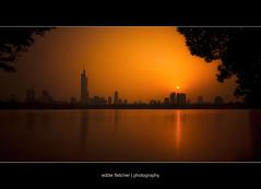 Blazing Skyline (eddie_fletch) Tags: china bw lake skyline reflections landscape long exposure cityscape angle 110 wide sigma filter prc lakeview nanjing ultra oldcity warming zhongshan sigma1020mm prchina lakesunset sigma1020 xuanwu hunanlu xuanwulake nd110 n