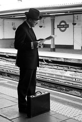 The English Man (longboy74) Tags: portrait bw london businessman commuter stationplatform readingthenewspaper manwearingahat 2010pictureaday tubelineinbackground briefcasebyfeet