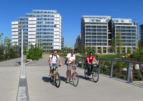 Three cyclists in front of the Olympic Village building at left where Canadian athletes had stayed
