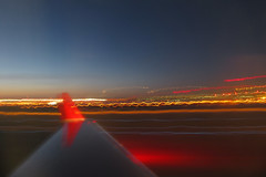 landing (Idle Type) Tags: travel red orange motion blur minnesota yellow night canon airplane lights evening airport streak dusk flight wing jet minneapolis fast powershot runway windowseat jetliner sx200 sx200is