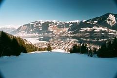 Zeller See (Ed.ward) Tags: trees sky lake holiday snow mountains alps film reflections austria town skiing superia zellamsee 2010 piste nikonf80 fujisuperia zellersee fb:uploaded=true fb:request=true nikkor20mmf28afd geo:lat=47321305 geo:lon=12786241
