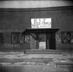 E&J (QsySue) Tags: door city blackandwhite building sign shop stairs mediumformat graffiti losangeles toycamera steps tags 120film brickwall uno storefront oops southcentrallosangeles southlosangeles fsck vernon vignetting nsb rl southcentral holga120fn ishm ilfordxp1120film c41developedinblackandwhitechemicals legstools
