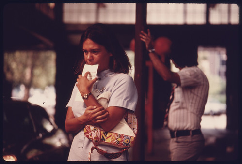 Student Nurse Stands Deep in Thought Waiting for Her Car to Complete Testing at an Auto Emission Inspection Station in Downtown Cincinnati, Ohio...09/1975