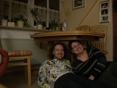 Margot and Peter Under the Table, Friday (traveling peter) Tags: pictures wood portrait people me window smiling wall shirt germany table bavaria chair friend girlfriend couple europe january livingroom indoors pottedplant margot friday heating pullover 2010 underthetable ochid mindelheim travelingpeter unterallgu year2010 margotsapartment meggiev unterallgaeucounty unterallgaeu