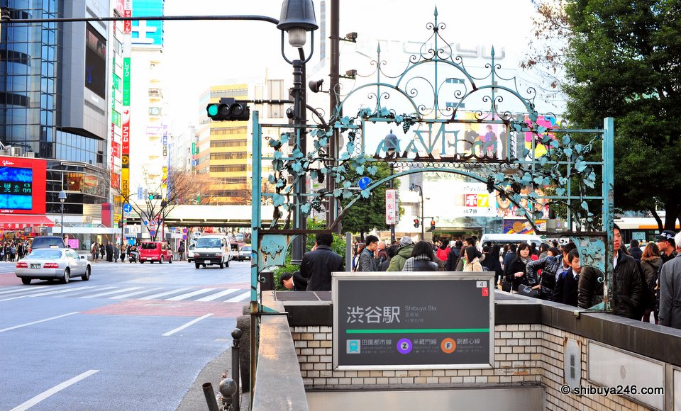 A different angle looking at Shibuya over the subway sign towards the Scramble Crossing.
