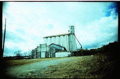 Old peanut plant in Fitzgerald, GA (anómyk) Tags: county camera plant building abandoned film rural 35mm ga georgia toy lomo xpro lomography crossprocessed junk exposure factory darkness cross cloudy kodak decay farm south toycamera grain wide deep full southern frame processing peanut process elitechrome expired vignetting vivitar processed ultra abandonment exposed fitzgerald plasticcamera uws deepsouth silm ultrawideslim benhill plasticlense rurex rurexing anomyk