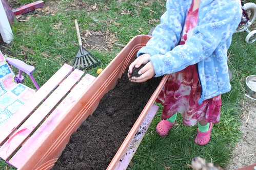 child filling a container garden