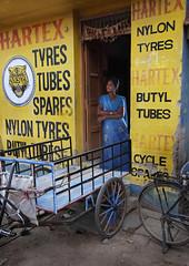 tyres, tubes and spares (Rick Elkins) Tags: woman india yellow standing typography bravo tires doorway cart sari madurai mywinners abigfave