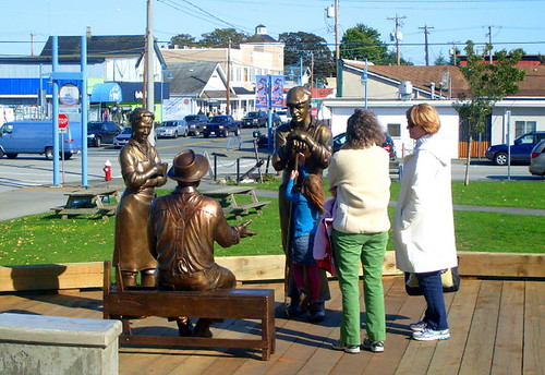 Life-size bronze figures of fishery workers with real people around them
