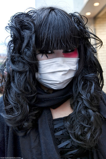 A Japanese girl in Harajuku with black hair, cool eye makeup, and a mask.