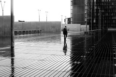 On the slippery boards (pascalcolin1) Tags: paris13 bnf homme man pluie rain reflets reflection planches boards glissant slippery photoderue streetview urbanarte noiretblanc blackandwhite photopascalcolin