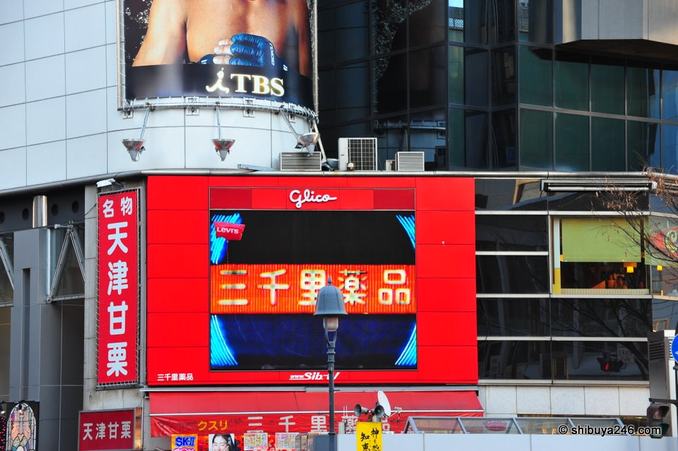 A LEVI'S balloon escaping a customers grip, takes a quick break for some free advertising in front of the glico electronic billboard.