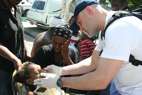 A member of the International Medical Corps treats a small child's injured eye outside a Port-au-Prince hospital.